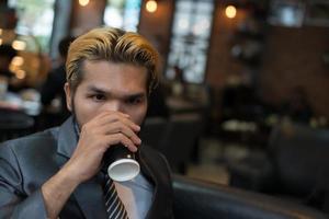 uomo d'affari che beve caffè nella caffetteria della città durante l'ora di pranzo foto