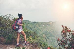 escursionista con zaino in piedi sulla cima di una montagna e godersi la vista della natura foto