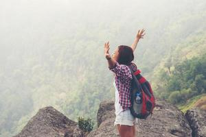 escursionista con zaino in piedi sulla cima di una montagna con le mani alzate foto