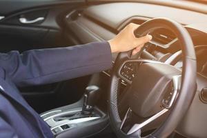 mano che tiene il volante in interni auto foto