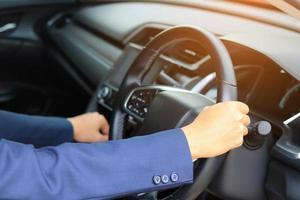 mani che tengono il volante in interni auto foto