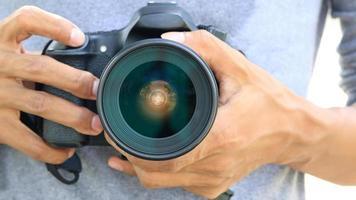 mani che tengono la fotocamera dslr foto