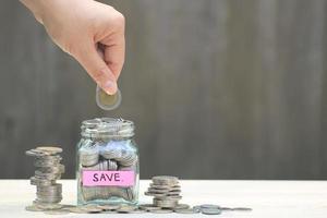 mano mettendo la moneta in un barattolo con l'etichetta salva accanto a pile di monete foto