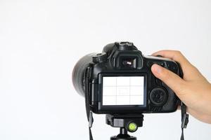 mano che regola la fotocamera reflex digitale dalla vista posteriore su sfondo bianco