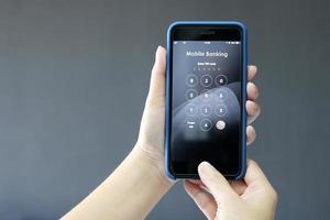mani che tengono il telefono cellulare con numeri di testo bancario mobile foto