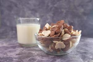 primo piano di fiocchi di mais al cioccolato e bicchiere di latte foto