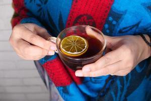 primo piano di una donna che beve il tè al limone foto