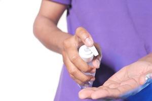uomo che utilizza liquido igienizzante per prevenire il virus corona foto