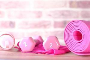 manubri colorati rosa, tappetino per esercizi e bottiglia d'acqua su sfondo di mattoni foto