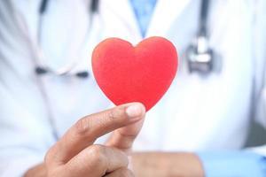 mano del medico che tiene un cuore rosso, primo piano