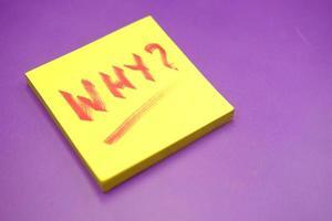 primo piano del punto interrogativo su carta su sfondo viola foto