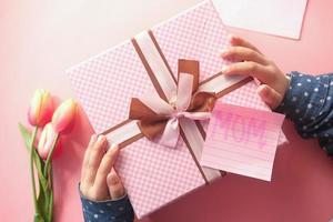concetto di festa della mamma della mano del bambino che tiene il contenitore di regalo di colore rosa foto