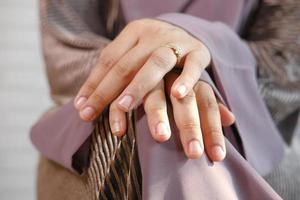 primo piano delle mani della donna con anello di nozze foto