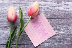 concetto di festa della mamma con fiori di tulipano e testo di mamma su una nota adesiva foto