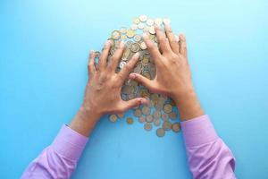 vista dall'alto delle mani dell'uomo che contano le monete sul colore di sfondo foto