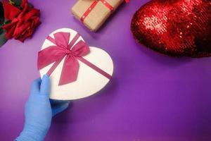 la mano maschio in un guanto medico blu dà un regalo