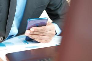 giovane che lavora sulla scrivania in ufficio e utilizza lo smartphone