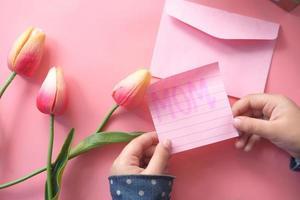 vista dall'alto della mano del bambino che tiene il regalo per la festa della mamma e il fiore in rosa foto