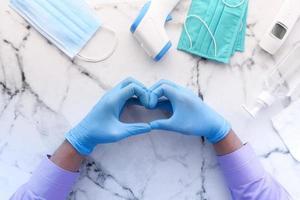 mano in guanti di lattice che mostra il simbolo a forma di cuore su sfondo di piastrelle foto