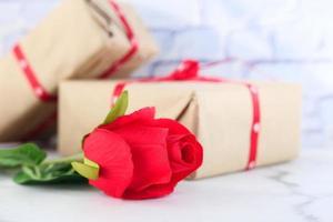 primo piano di rosa rossa e pila di confezione regalo sul tavolo foto