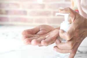 primo piano della donna senior utilizzando gel disinfettante per le mani per prevenire il virus foto