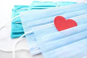 maschere chirurgiche a forma di cuore e disinfettante per le mani su sfondo bianco foto