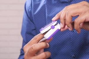 primo piano della mano d'uomo utilizzando un pulsossimetro foto