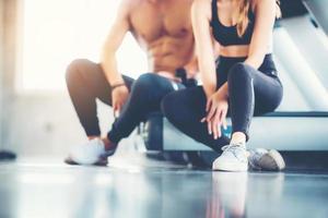 immagine sfocata dell'uomo e della donna in abbigliamento sportivo seduti in una palestra con una sola scarpa a fuoco