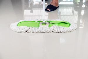 persona con la polvere mop spazzare il pavimento di piastrelle foto