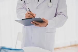 medico maschio con camice da laboratorio e stetoscopio tenendo appunti e penna