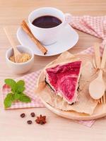 torta di lamponi con caffè su uno sfondo di legno foto