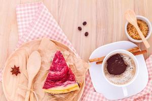 torta di lamponi con una tazza di caffè su fondo in legno foto