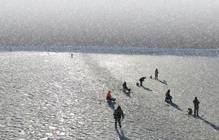 persone che pescano sul ghiaccio nella neve foto