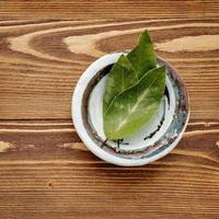 foglie di alloro in una ciotola su fondo di legno squallido foto