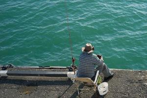 uomo seduto e pesca su un molo foto