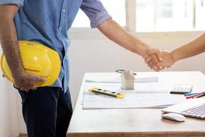 team di architettura stringe la mano nella costruzione di edifici foto