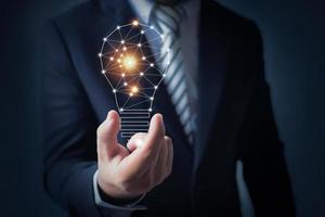 concetto di innovazione, uomo d'affari in possesso di una lampadina foto