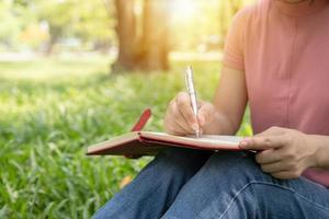 persona che scrive in un diario foto