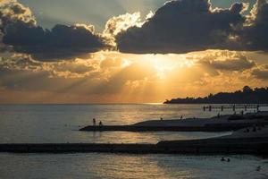 persone che si stagliano su una spiaggia con cielo nuvoloso al tramonto foto