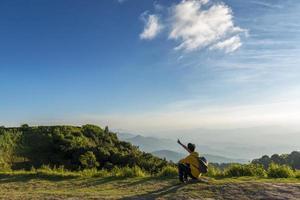 uomo viaggiatore seduto sulla roccia con sfondo di montagne foto