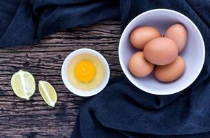 uova fresche in una ciotola sul vecchio tavolo di legno. foto