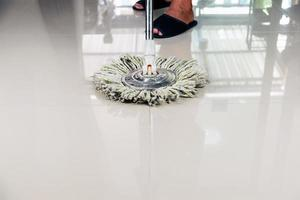 persona che pulisce un pavimento di piastrelle con una scopa antipolvere foto