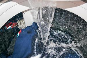 primo piano di una lavatrice versando acqua sui vestiti foto