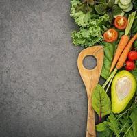 cucchiaio di legno e verdure su sfondo di pietra scura foto