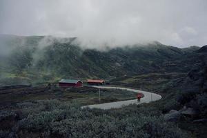 ciclista che guida nelle montagne nebbiose verso il granaio rosso foto