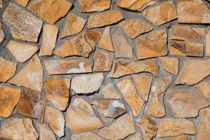 Priorità bassa strutturata del muro di pietra arancione foto