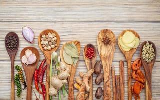 erbe aromatiche e spezie in cucchiai su uno sfondo di legno chiaro foto