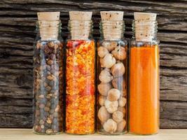 bottiglie di spezie su uno sfondo di legno rustico foto