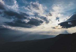 la vista del sole sta per tramontare su un'alta montagna foto