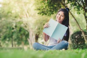una donna seduta e leggendo un libro in giardino foto